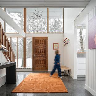 Réalisation d'un hall d'entrée vintage avec un mur blanc, béton au sol, une porte simple, une porte en bois brun et un sol gris.