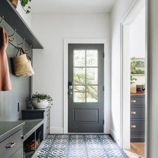Inspiration for a transitional porcelain tile and black floor entryway remodel in Grand Rapids with white walls and a black front door