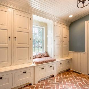 Bild på ett vintage kapprum, med blå väggar, tegelgolv, en enkeldörr, en vit dörr och rött golv