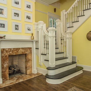 Example of an eclectic medium tone wood floor entryway design in Charleston with yellow walls and a white front door