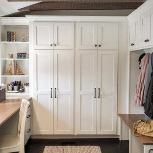 Immagine di un piccolo ingresso con anticamera country con pareti bianche, pavimento con piastrelle in ceramica, una porta singola, una porta in legno bruno, pavimento grigio, travi a vista e pareti in perlinato