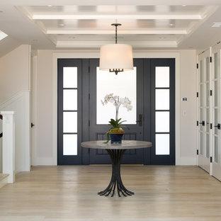サンディエゴの広い片開きドアトランジショナルスタイルのおしゃれな玄関ロビー (淡色無垢フローリング、黒いドア、白い壁、ベージュの床) の写真