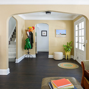 Entryway - mid-sized traditional dark wood floor entryway idea in Minneapolis with yellow walls and a white front door