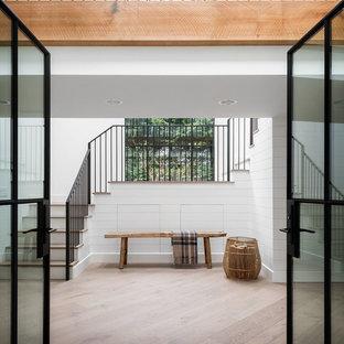 Idée de décoration pour une entrée champêtre avec un mur blanc, une porte double, une porte noire et du lambris de bois.