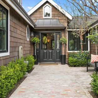 オレンジカウンティのダッチドアトランジショナルスタイルのおしゃれな玄関ドア (茶色い壁、レンガの床、黒いドア) の写真