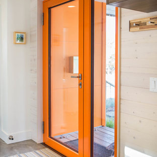 Entryway - small contemporary concrete floor and gray floor entryway idea in Other with white walls and an orange front door
