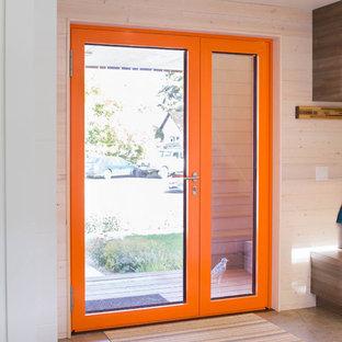 Inspiration för en liten funkis ingång och ytterdörr, med vita väggar, betonggolv, en enkeldörr, en orange dörr och grått golv