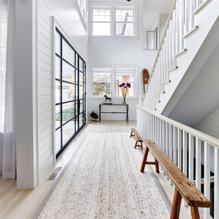 Huge coastal light wood floor entryway photo in New York with white walls and a glass front door