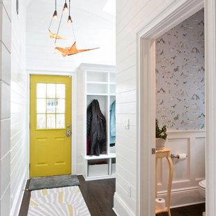 Foto di un corridoio costiero con pareti bianche, parquet scuro, una porta singola e una porta gialla
