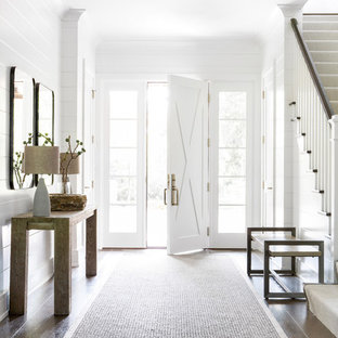 Idée de décoration pour un hall d'entrée champêtre de taille moyenne avec un mur blanc, un sol en bois foncé, une porte simple et une porte blanche.