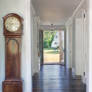 Example of a country dark wood floor entryway design in DC Metro with gray walls and a glass front door