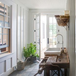 На фото: прихожая в стиле кантри с белыми стенами, стеклянной входной дверью и полом из сланца с