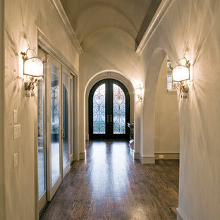 Mid-sized tuscan dark wood floor and brown floor entryway photo in Dallas with beige walls and a metal front door