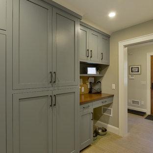 ニューヨークの大きい片開きドアトランジショナルスタイルのおしゃれなマッドルーム (グレーの壁、磁器タイルの床、木目調のドア、ベージュの床) の写真