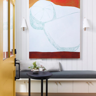 サンフランシスコの中くらいの片開きドアカントリー風おしゃれな玄関ドア (白い壁、無垢フローリング、黄色いドア、塗装板張りの壁) の写真