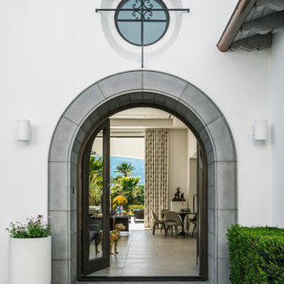 Small tuscan porcelain floor and gray floor entryway photo in Los Angeles with white walls and a glass front door