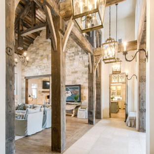 Ispirazione per un ampio corridoio country con pareti bianche, pavimento in pietra calcarea, una porta a due ante, una porta nera e pavimento beige
