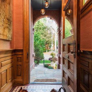 トロントの小さい片開きドアエクレクティックスタイルのおしゃれな玄関ドア (淡色無垢フローリング、木目調のドア、ピンクの壁) の写真