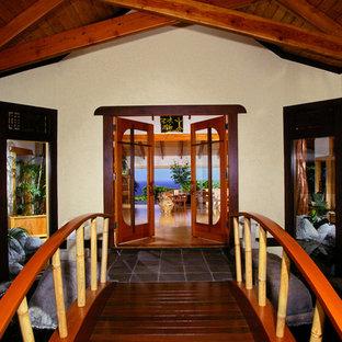Immagine di un ingresso o corridoio tropicale con pareti beige e una porta a due ante