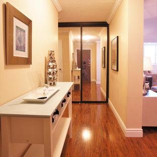 Inspiration pour un petit hall d'entrée traditionnel avec un mur beige, un sol en vinyl, une porte simple et une porte en bois brun.