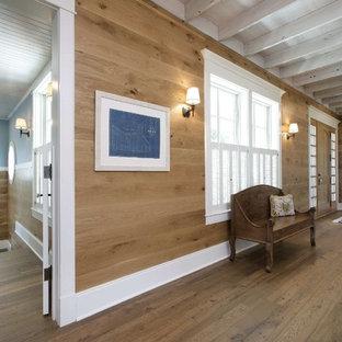 Réalisation d'une entrée tradition avec un couloir, un mur bleu, un sol en bois brun, une porte simple et une porte blanche.