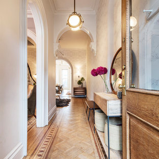 Design ideas for a transitional entry hall in New York with white walls, light hardwood floors, a single front door, a medium wood front door and brown floor.