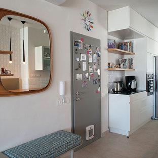 Cette photo montre une entrée tendance avec un mur blanc, une porte simple et une porte métallisée.