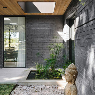 Large trendy limestone floor, gray floor, wood ceiling and brick wall entryway photo in Austin with black walls and a black front door
