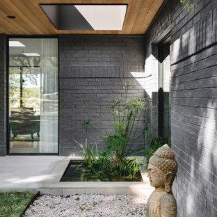 Idéer för att renovera en stor funkis ingång och ytterdörr, med svarta väggar, kalkstensgolv, en enkeldörr, en svart dörr och grått golv