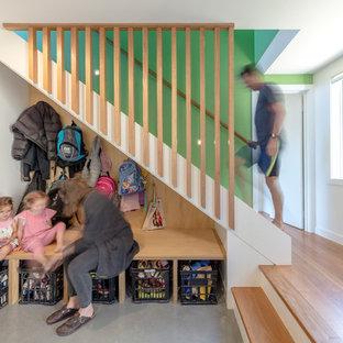 Exemple d'une petit entrée tendance avec un vestiaire, un mur blanc, un sol en bambou, une porte double, une porte rouge et un sol marron.