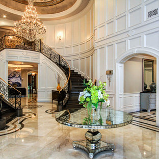 Example of a huge classic marble floor foyer design in Los Angeles with white walls