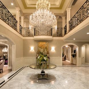На фото: класса люкс огромные фойе в стиле современная классика с серыми стенами и мраморным полом