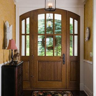 Diseño de puerta principal clásica, grande, con paredes amarillas, suelo de madera oscura, puerta simple y puerta de madera en tonos medios