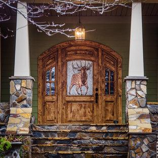 Modelo de puerta principal de estilo americano, grande, con parades naranjas, puerta simple, suelo marrón, suelo de madera clara y puerta de madera en tonos medios