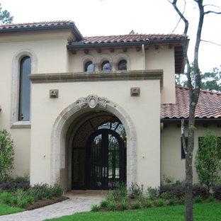 Immagine di un'ampia porta d'ingresso con pareti beige, pavimento alla veneziana, una porta a due ante e una porta in vetro