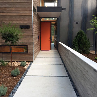 Example of a trendy concrete floor entryway design in Denver with brown walls and an orange front door
