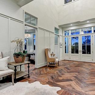 Aménagement d'un très grand hall d'entrée campagne avec un mur blanc, un sol en bois brun, une porte double, une porte grise et un sol marron.