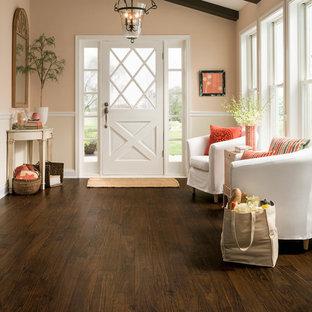 他の地域の中サイズの片開きドアトランジショナルスタイルのおしゃれな玄関ロビー (ピンクの壁、濃色無垢フローリング、白いドア) の写真