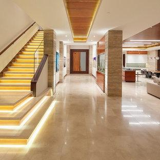 Idéer för en mycket stor modern ingång och ytterdörr, med beige väggar, granitgolv och mellanmörk trädörr