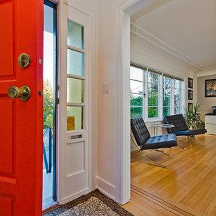 Immagine di un piccolo ingresso o corridoio minimalista con pareti gialle, parquet chiaro e una porta singola