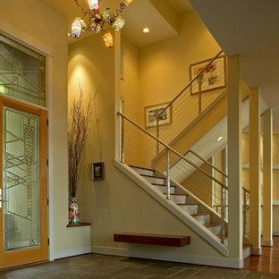 Immagine di una grande porta d'ingresso design con pareti gialle, una porta a due ante, una porta in vetro e pavimento in gres porcellanato