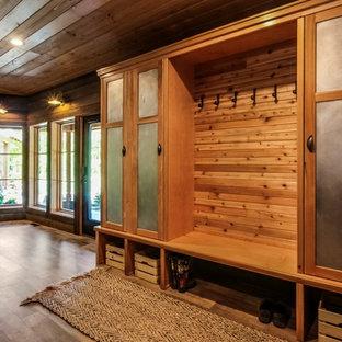 Idée de décoration pour une entrée chalet de taille moyenne avec un vestiaire, un mur marron, un sol en vinyl, une porte simple, une porte en verre et un sol marron.