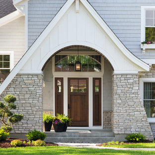Exempel på en stor klassisk ingång och ytterdörr, med betonggolv och mörk trädörr