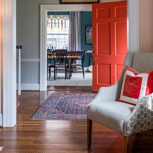 ローリーの中サイズのエクレクティックスタイルのおしゃれな玄関ドア (グレーの壁、無垢フローリング、オレンジのドア、茶色い床) の写真