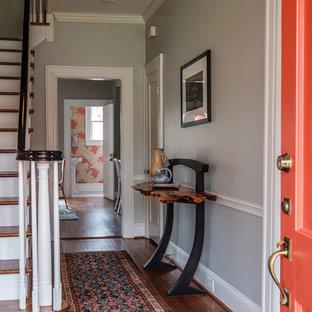 ローリーの片開きドアエクレクティックスタイルのおしゃれな玄関ロビー (グレーの壁、無垢フローリング、オレンジのドア、茶色い床) の写真