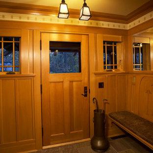 Idéer för att renovera en amerikansk farstu, med gula väggar, skiffergolv, en enkeldörr och mellanmörk trädörr