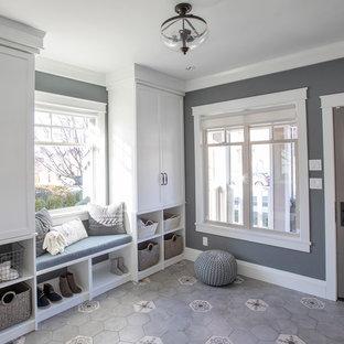 Exempel på ett mellanstort klassiskt kapprum, med grå väggar, en enkeldörr och en brun dörr