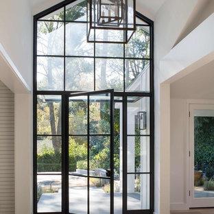 Ejemplo de puerta principal de estilo de casa de campo, grande, con paredes blancas, suelo de madera clara, puerta simple, puerta negra y suelo marrón