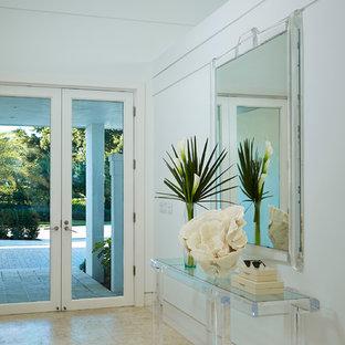 Exemple d'une porte d'entrée tendance avec un mur blanc, un sol en bois clair, une porte double et une porte blanche.
