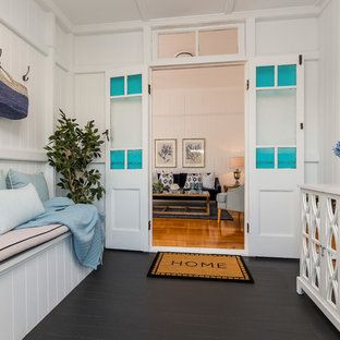 This is an example of a beach style vestibule in Brisbane with white walls, painted wood floors and black floor.